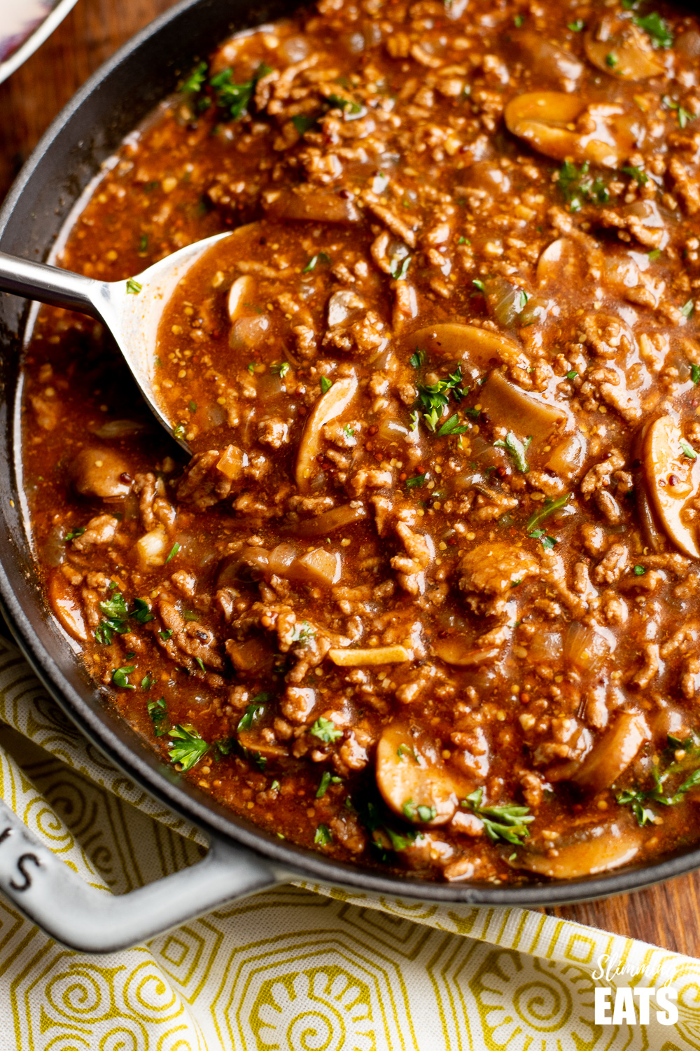close up of mustard beef with mushrooms in a grey cast iron pan