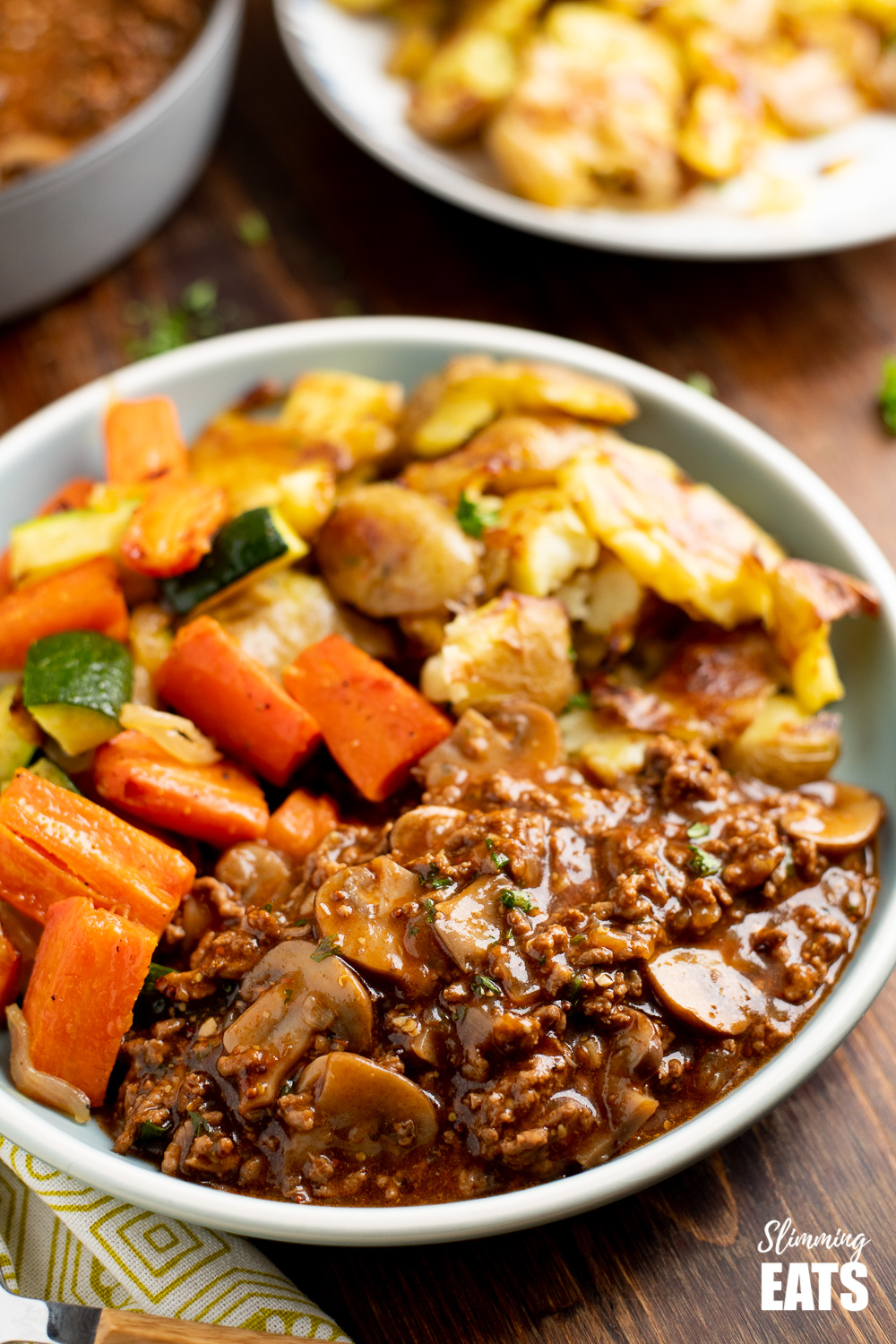 mushroom beef with mushrooms on a blue plate with vegetables and crushed potatoes