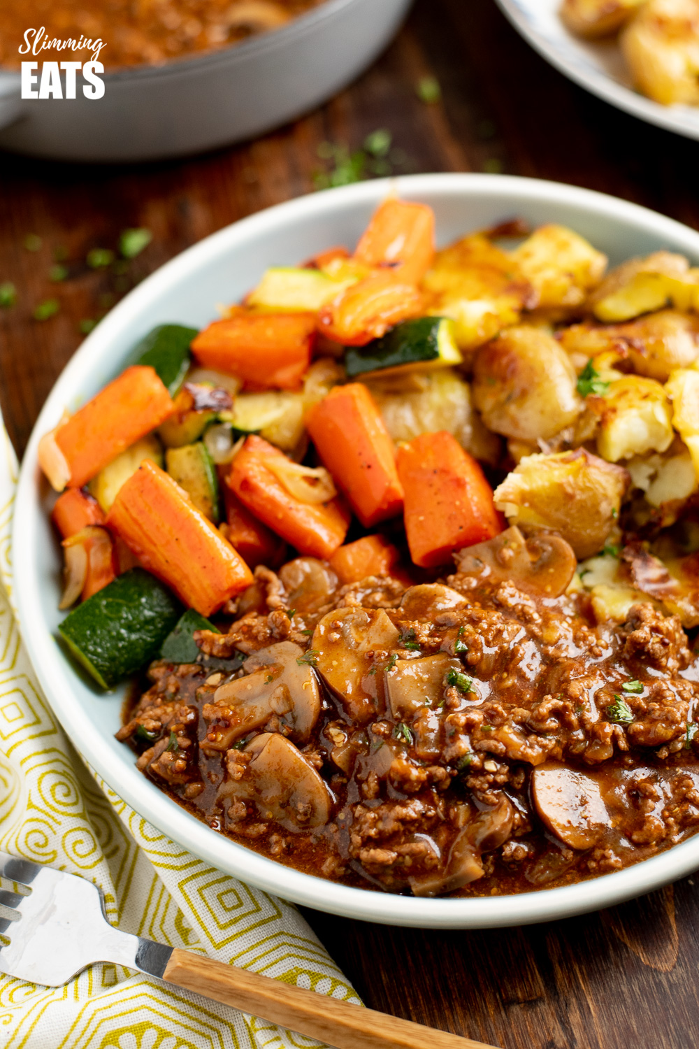 mustard beef with mushrooms on a blue plate with crushed roasted potatoes and vegetables