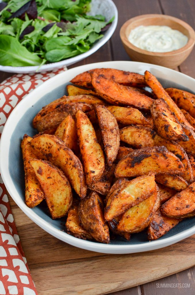 spicy potato wedges in a bowl with garlic mayo and baby greens in the background