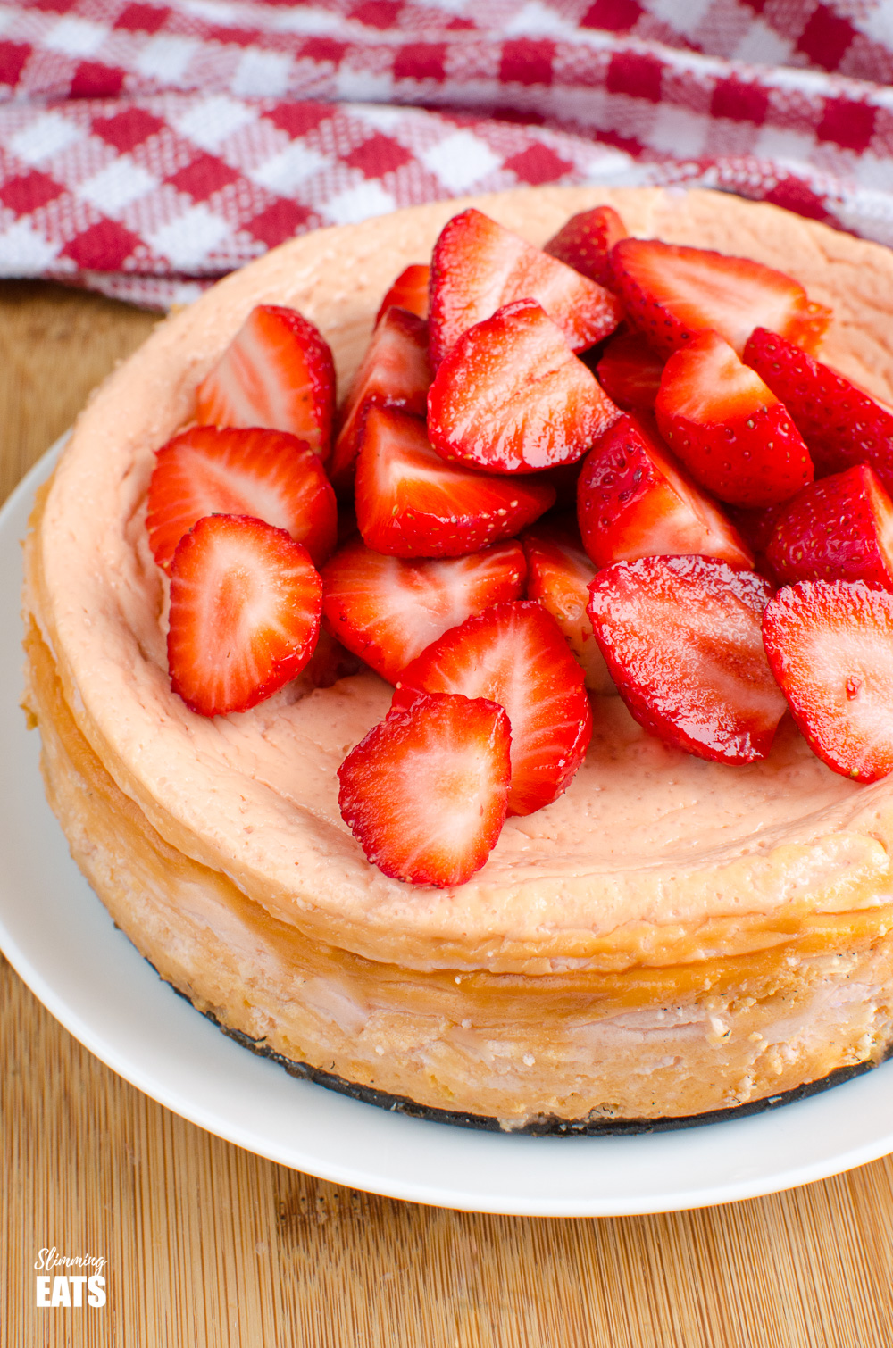 baked strawberry cheesecake on white plate with red chequed towel behind