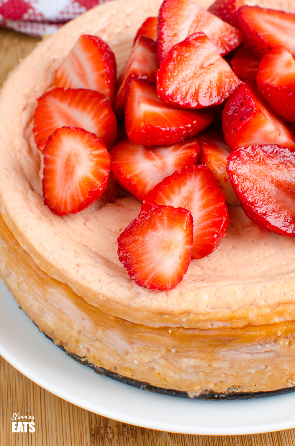 close up of baked strawberry cheesecake on white plate