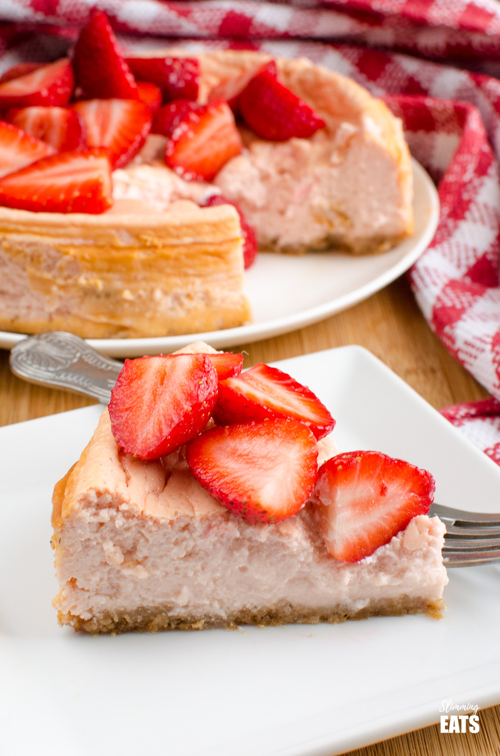 slice of baked strawberry cheesecake on white plate