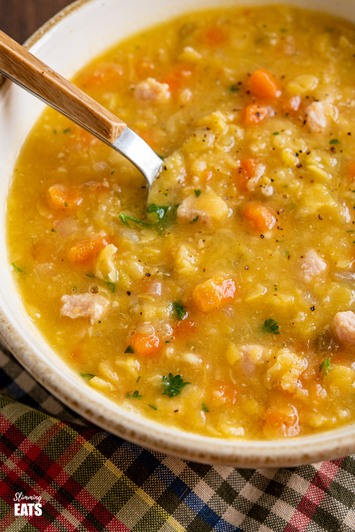 close up of split pea and bacon soup in bowl with wooden handles spoon