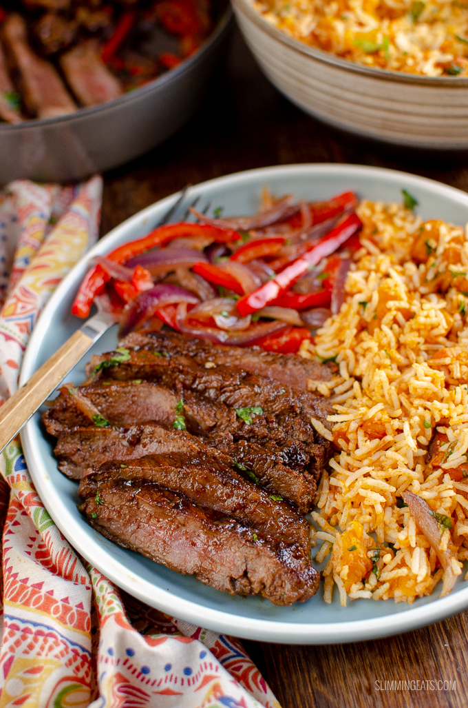 marinated mouth-watering steak on grey blue plate with peppers, onion and roasted butternut squash rice