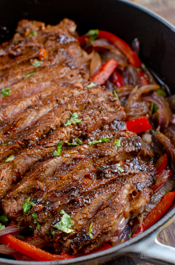 close up of Marinated Mouth-Watering Steak in cast iron skillet with peppers and onion