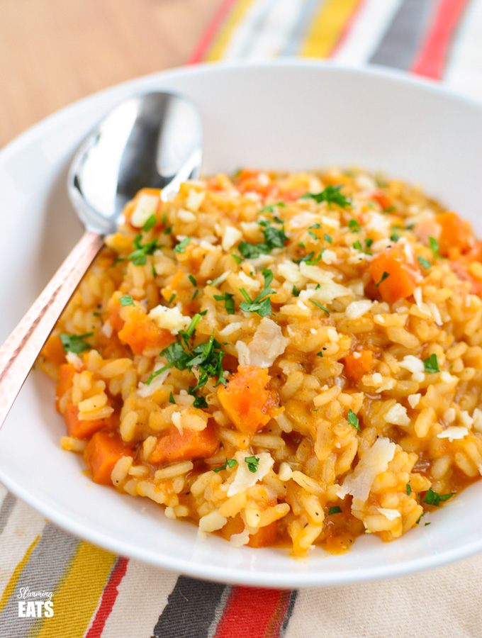roasted butternut squash risotto in white bowl with rose gold handled spoon