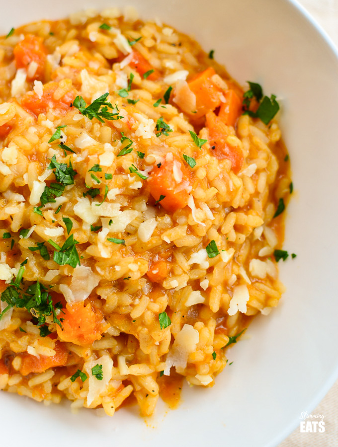 roasted butternut squash risotto sprinkled with fresh parsley in white bowl