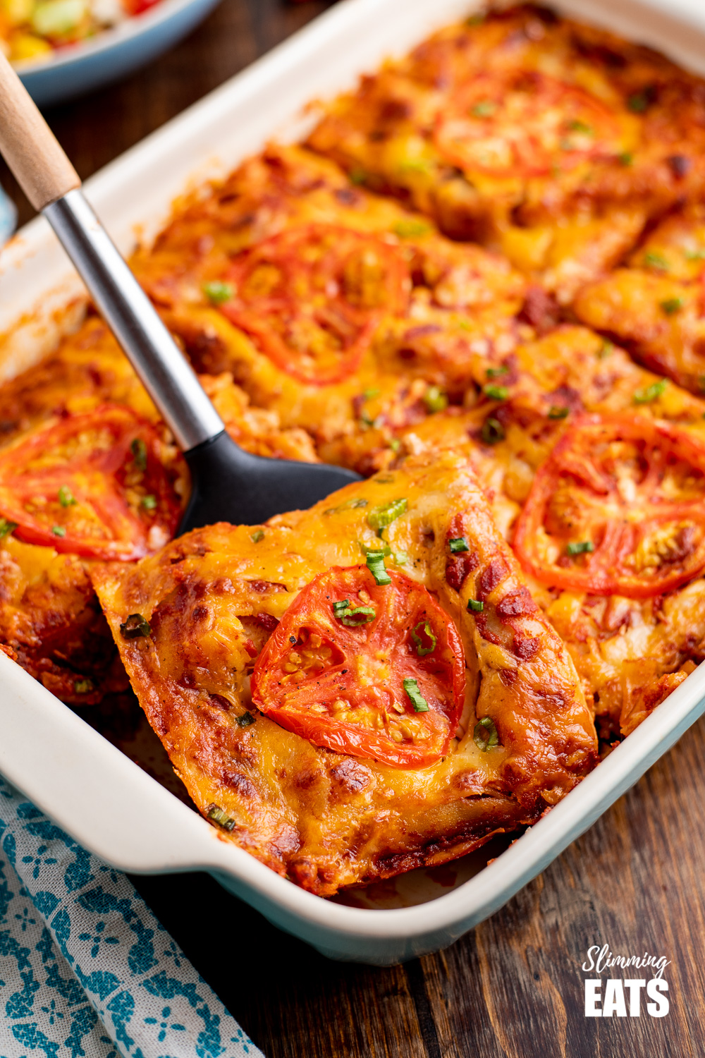 close of slice of spicy Mexican chicken lasagne on spatula with wooden handle