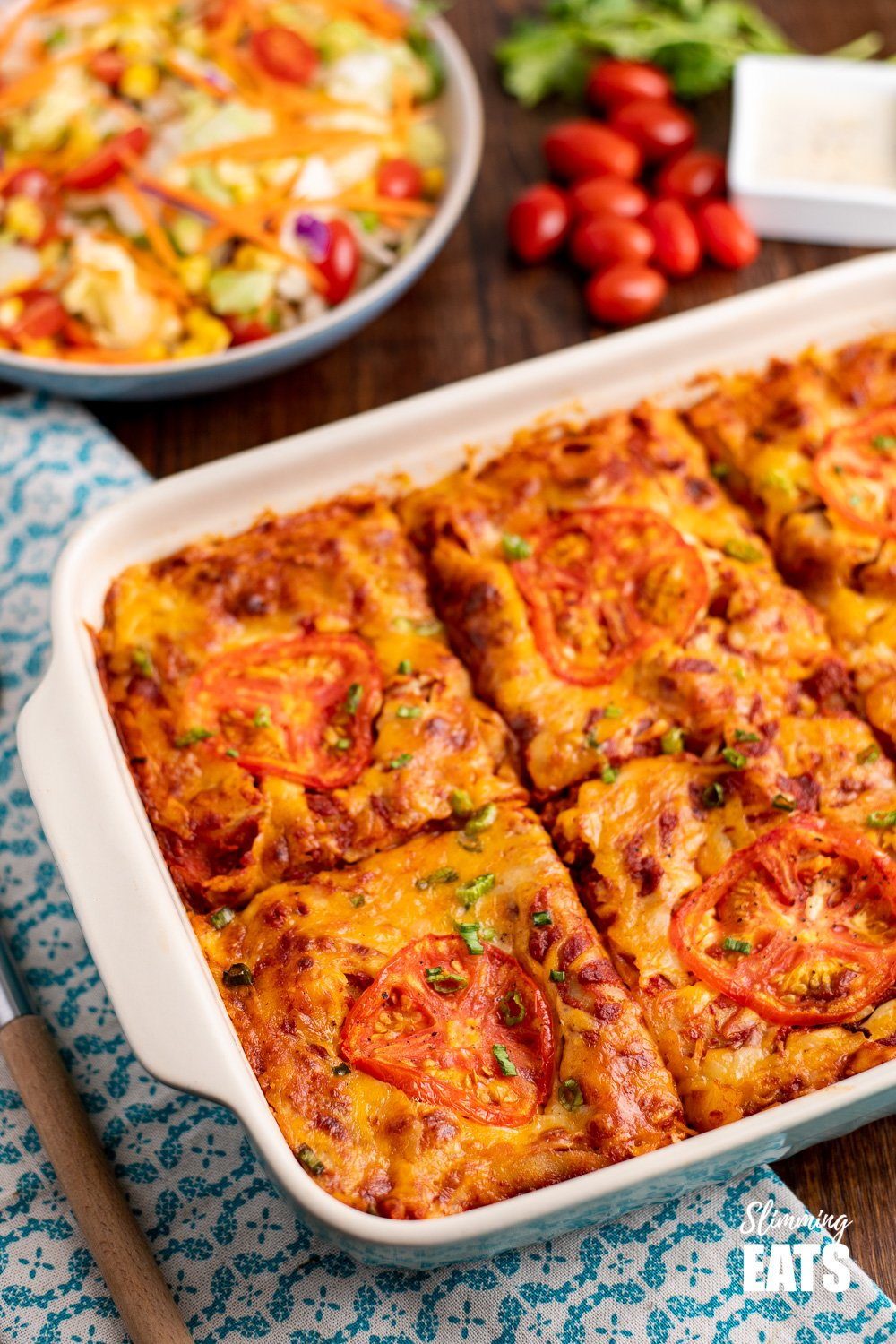 spicy Mexican chicken lasagne in oven proof dish with salad and tomatoes in background