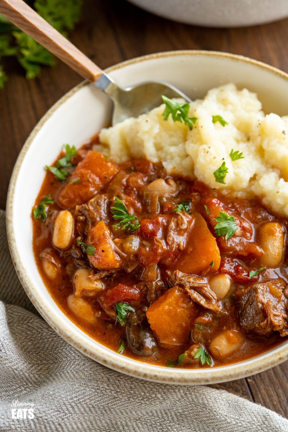 close up of Tuscan Beef Casserole in cream bowl with cauliflower mash