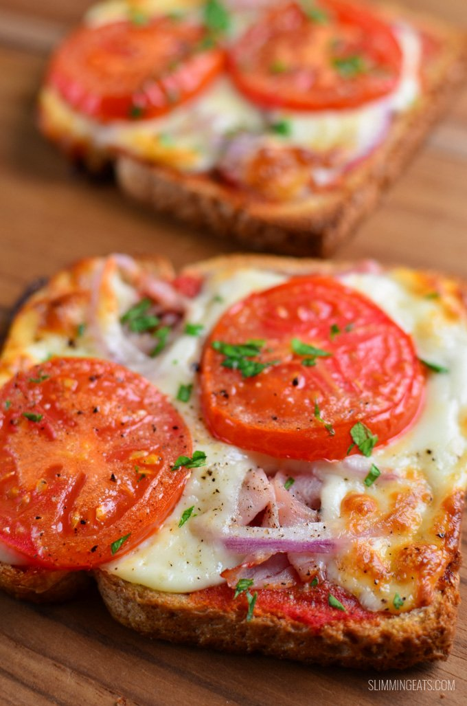 close up on two pizza toasts on a wooden board.