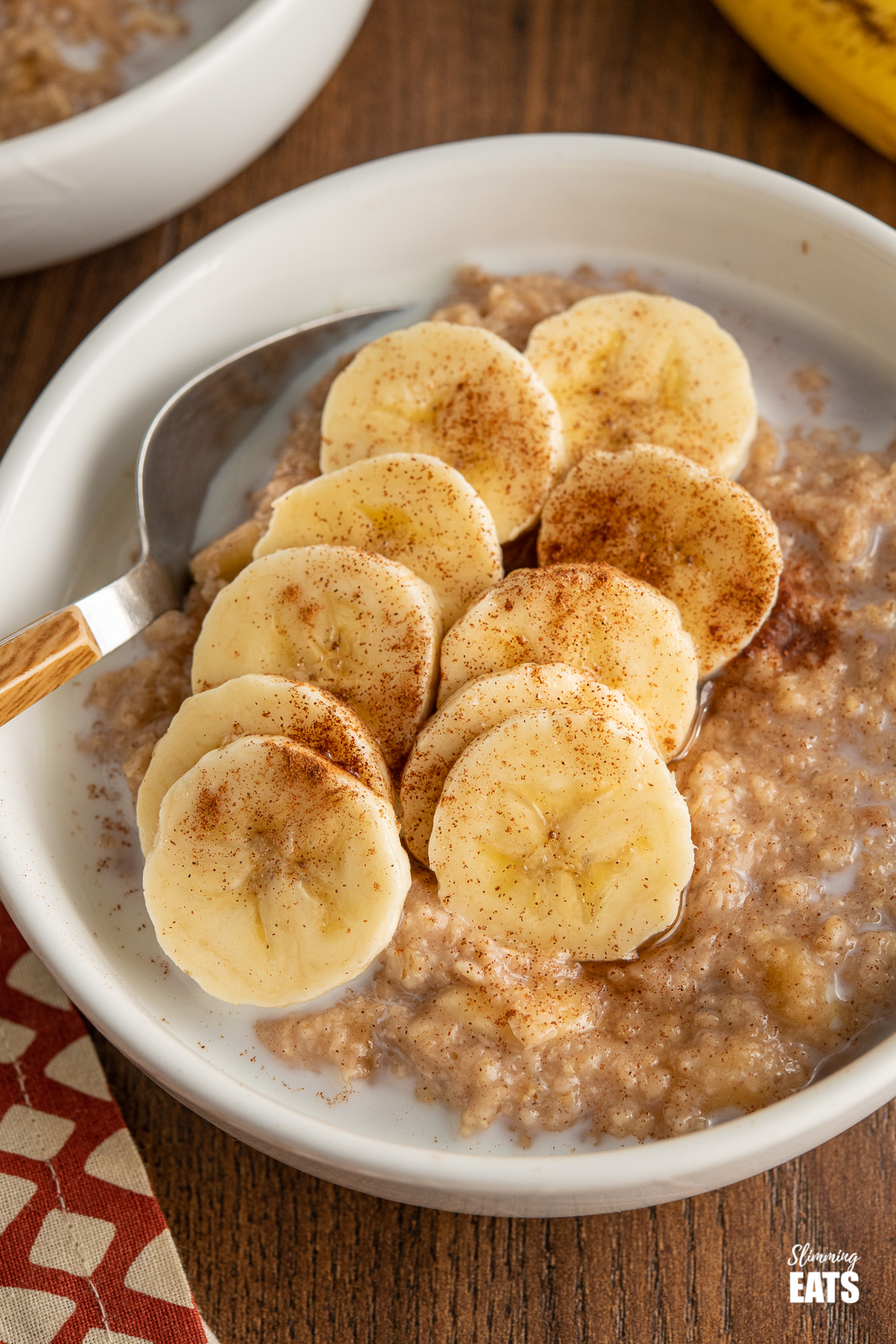 close up of Oatmeal with Banana, Cinnamon and Maple Syrup in white bowl