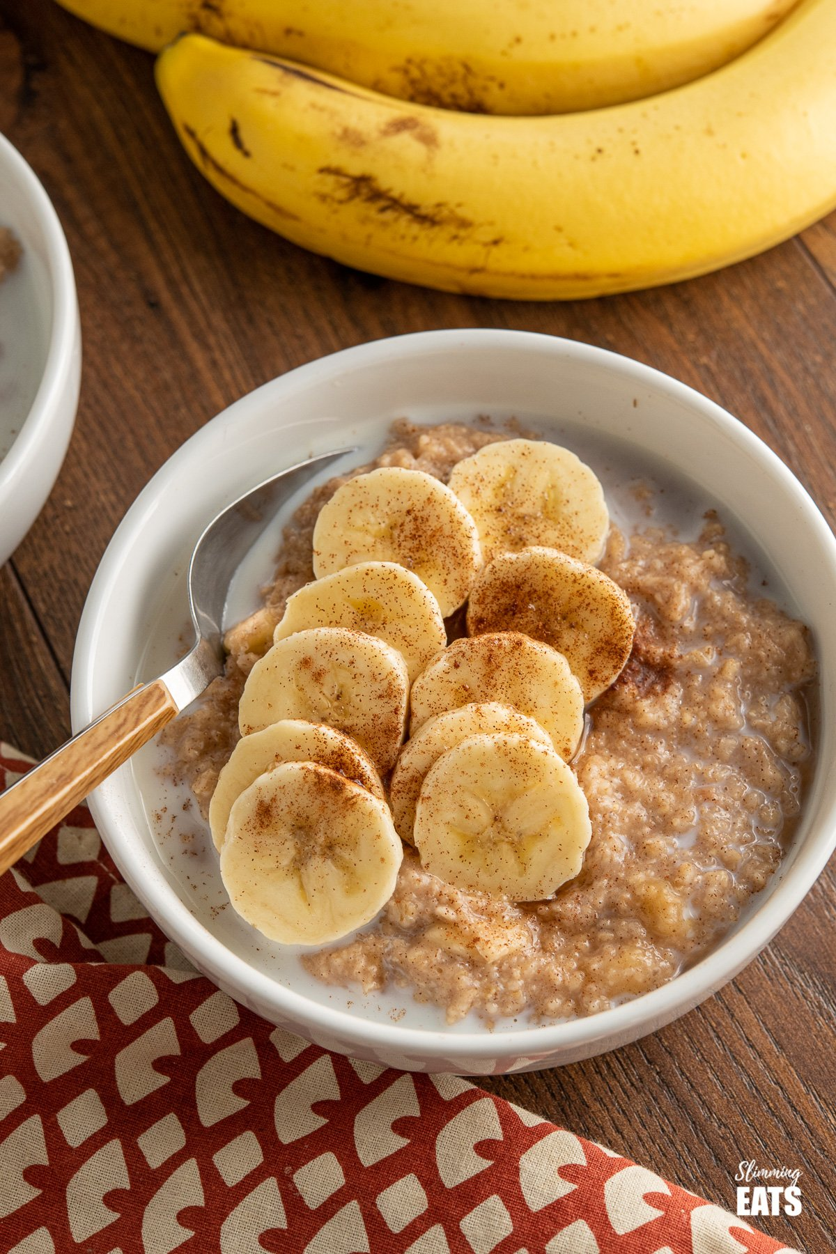 Oatmeal with Banana, Cinnamon and Maple Syrup in white bowl with wooden handled spoon and bananas in background