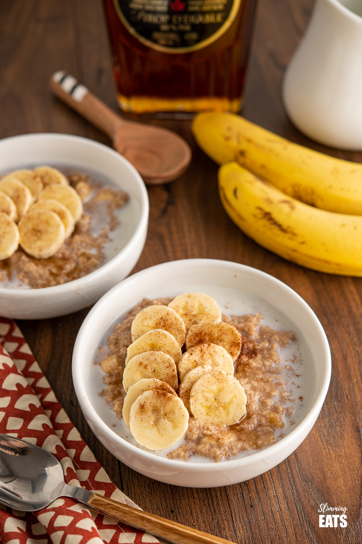 two bowls of creamy milky oatmeal topped with slices of banana, cinnamon and a drizzle of maple syrup, two banans and maple syrup bottle in the background