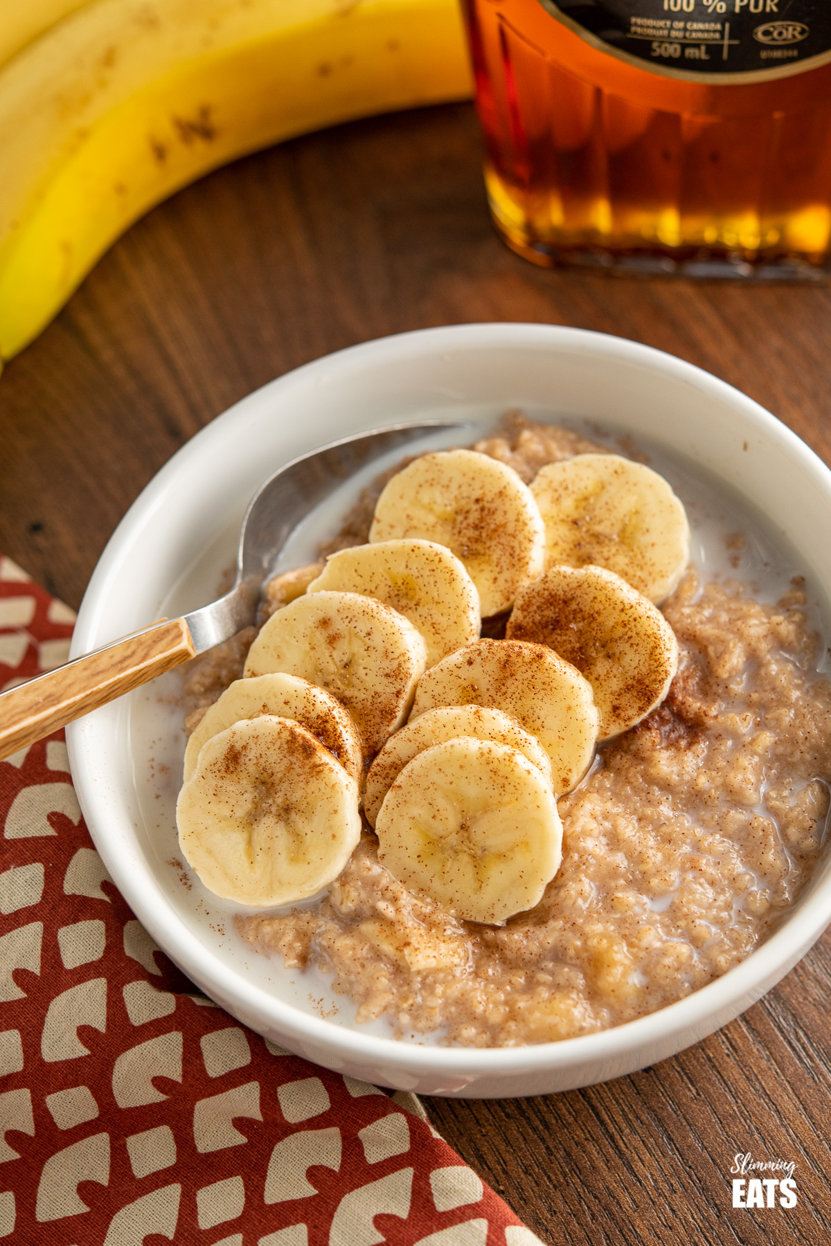 bowl of creamy milky banana cinnamon maple oatmeal with wooden handled spoon and banana and maple syrup bottle in the background