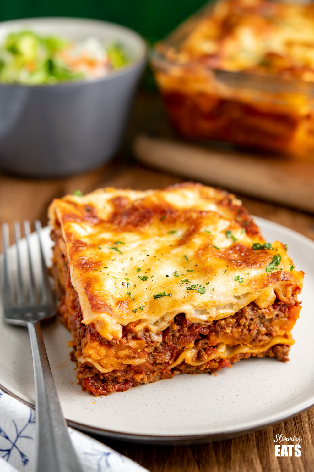beef lasagne on cream plate with silver fork - salad and lasagne in background.