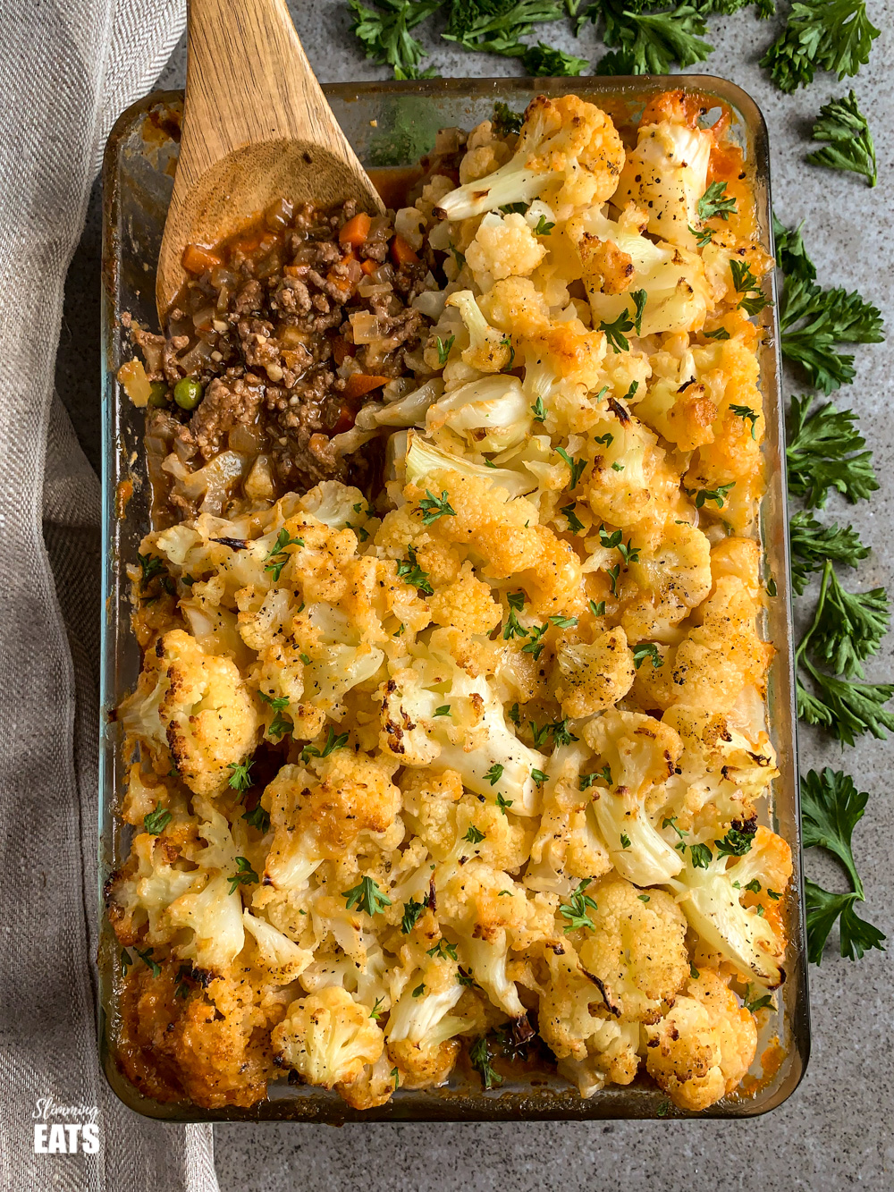 wooden spoon scooping Cheesy Cauliflower Topped Pie from a glass oven dish