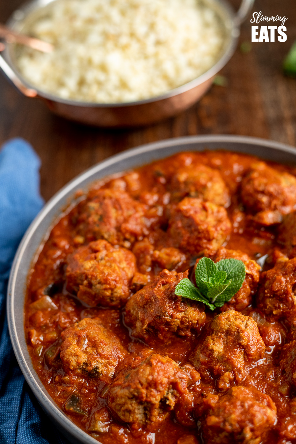 lamb and mint meatballs in a sweet and spicy sauce in a grey bowl on wooden board