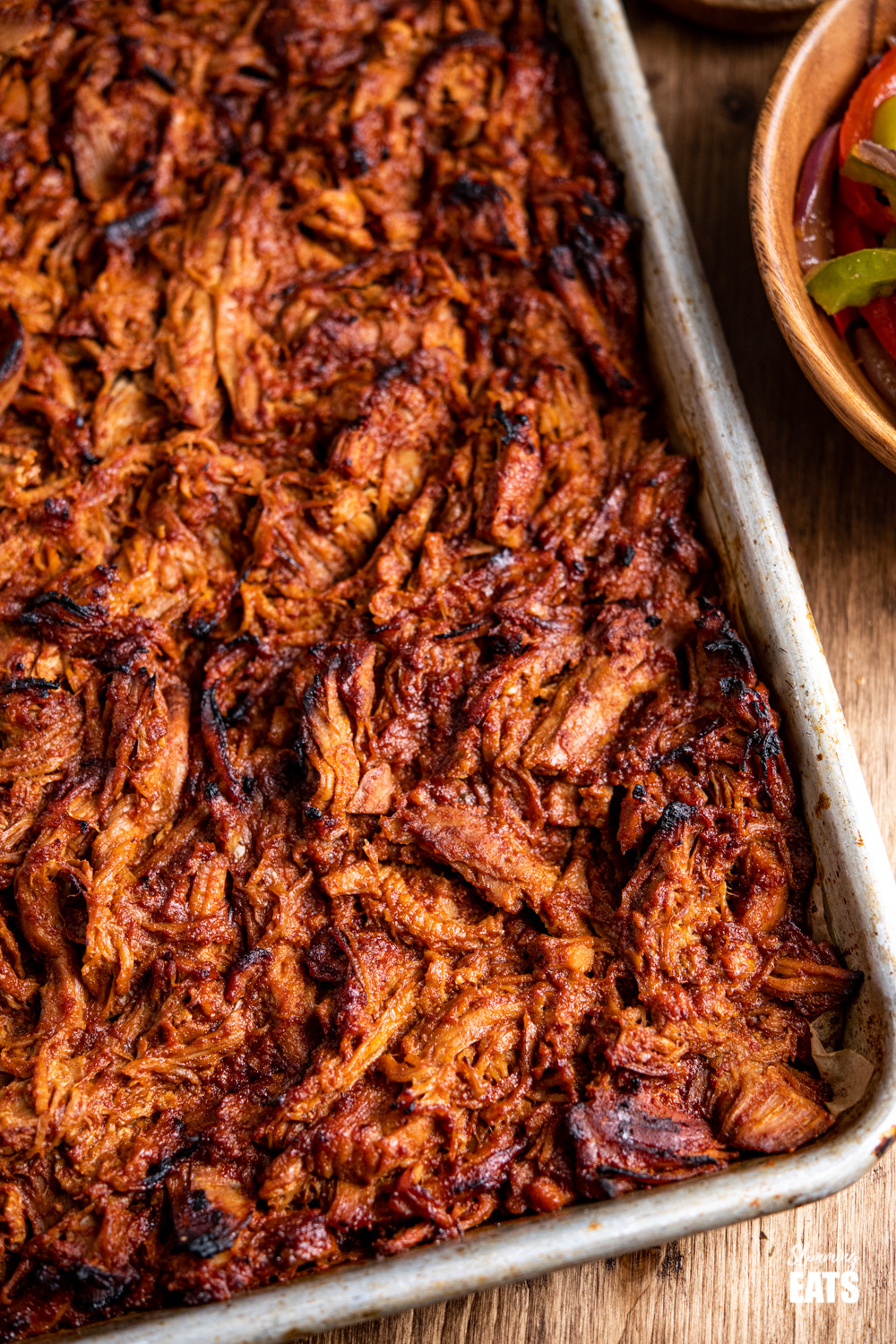 close up of slow cooker pulled pork caramelised on baking tray