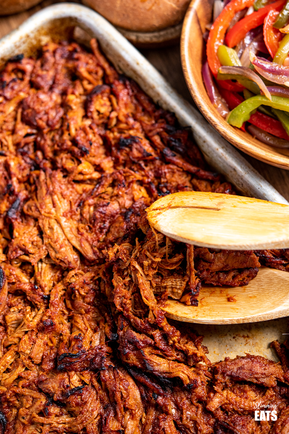 slow cooker pulled pork on baking tray with wooden tonges and bowl of peppers and onion