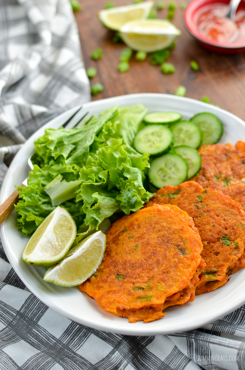 low Syn Thai Crab Cakes on a white plate with lettuce, cucumber and lime slices