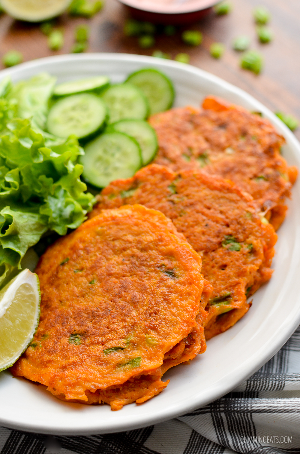 3 thai crab cakes on a white plate with salad and cucumber
