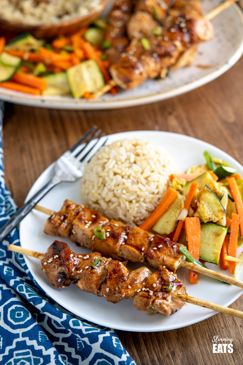Yakitori Chicken Skewers on white plate with serving brown rice and sesame vegetables