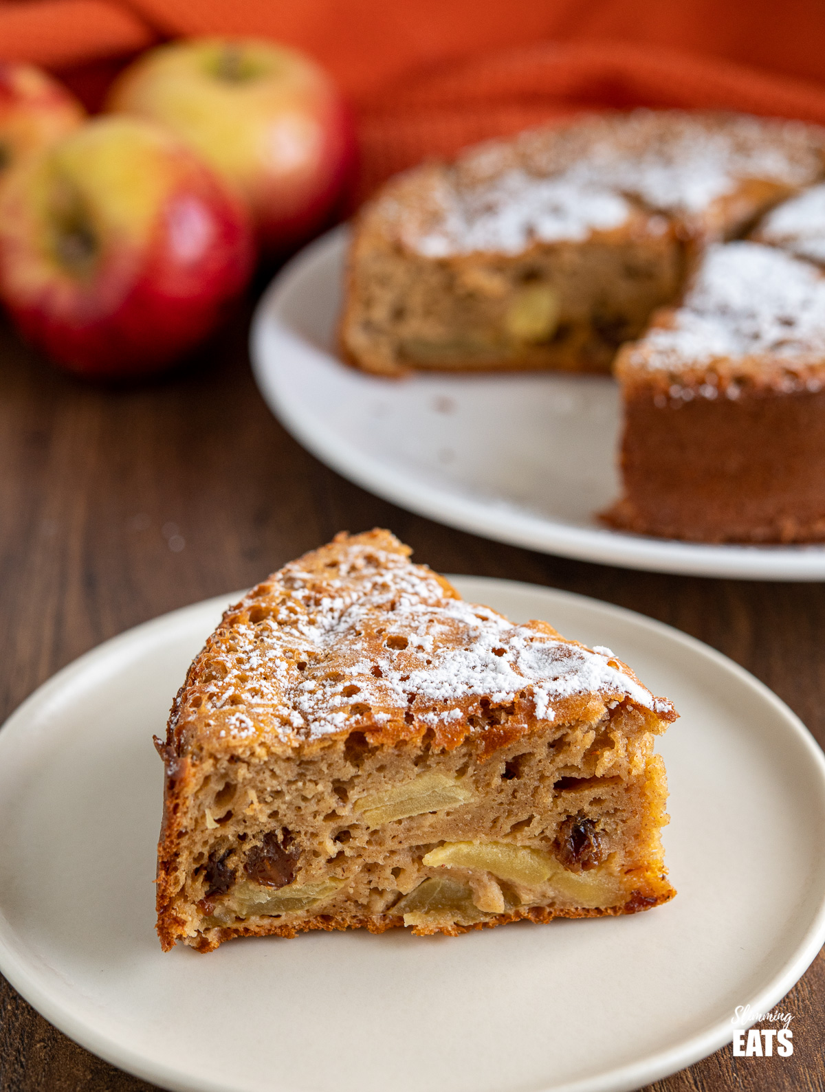 slice of apple sultana cake on white plate with cake and apples in background