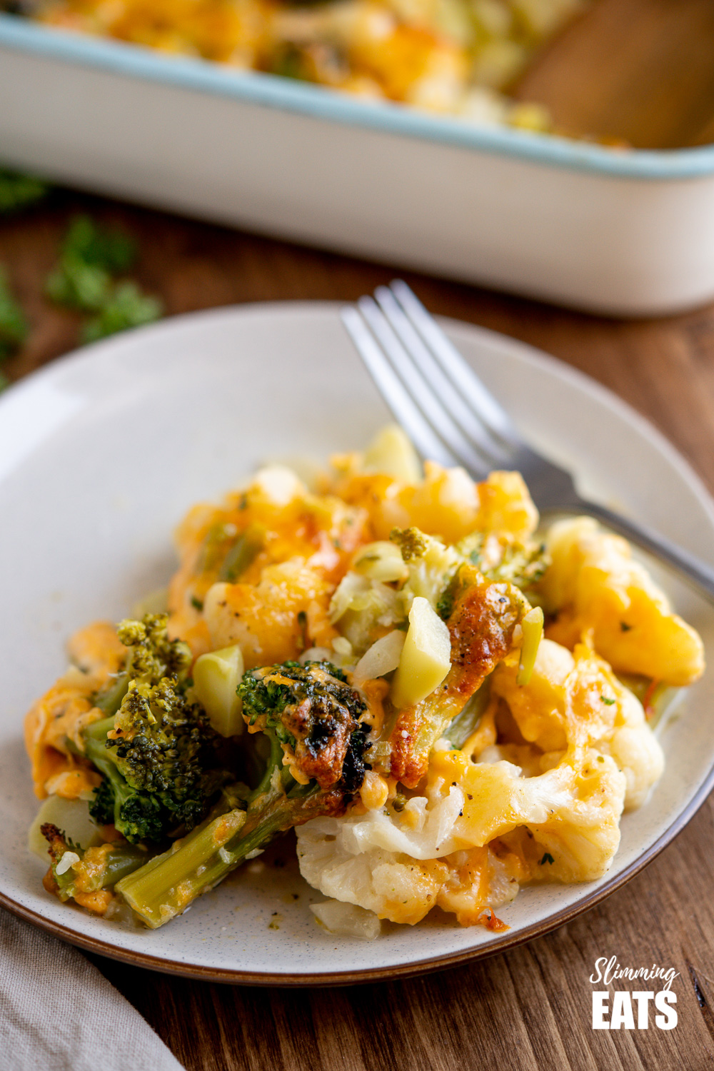 serving of Creamy Cheesy Vegetable Bake on cream coloured plate with brown rim