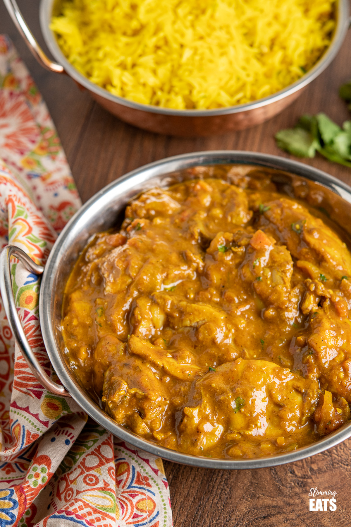 Chicken Dopiaza in metal dish with pilau rice in background