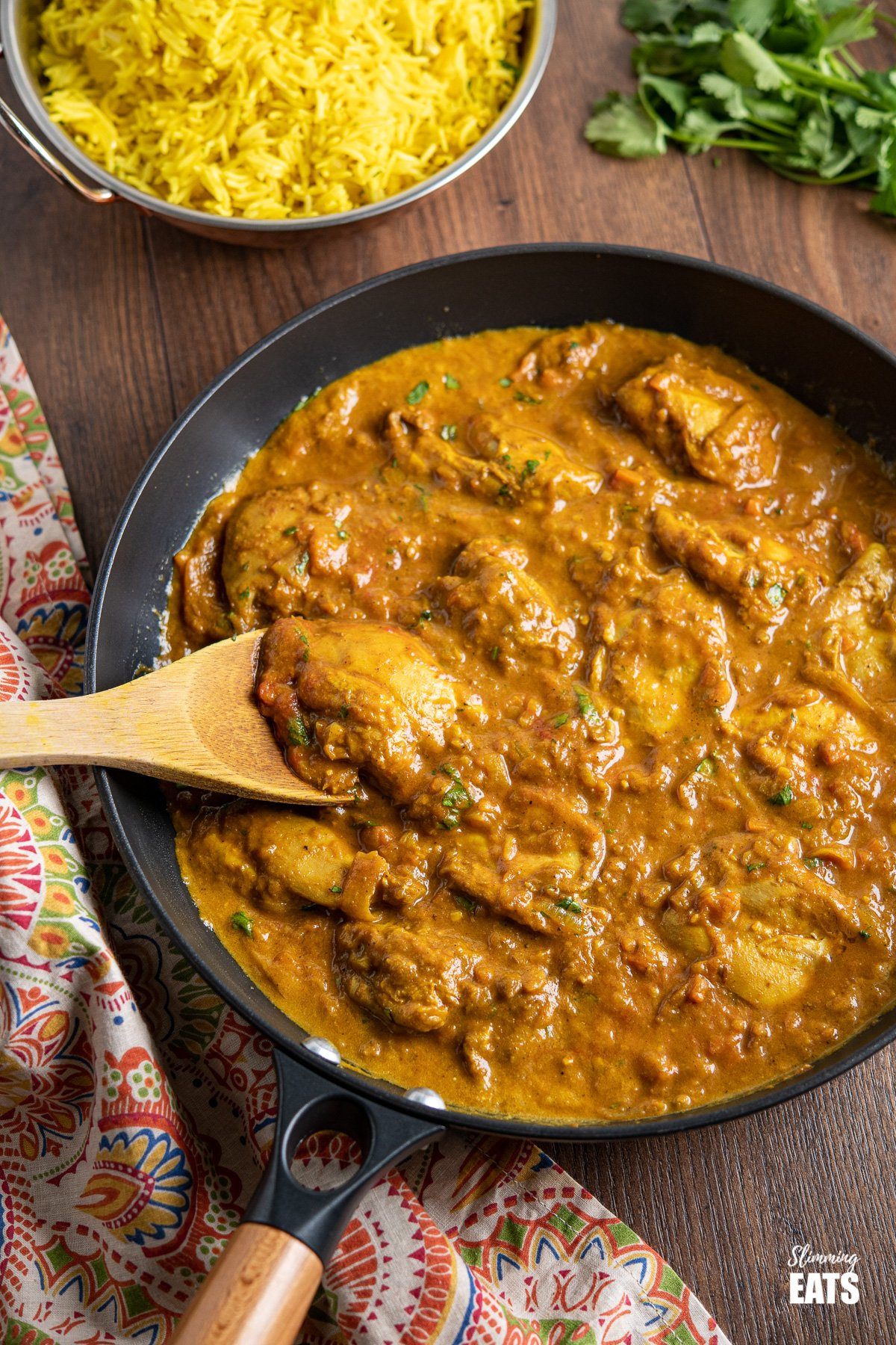 Chicken Dupiaza in black frying pan with wooden handle, pilau rice in background