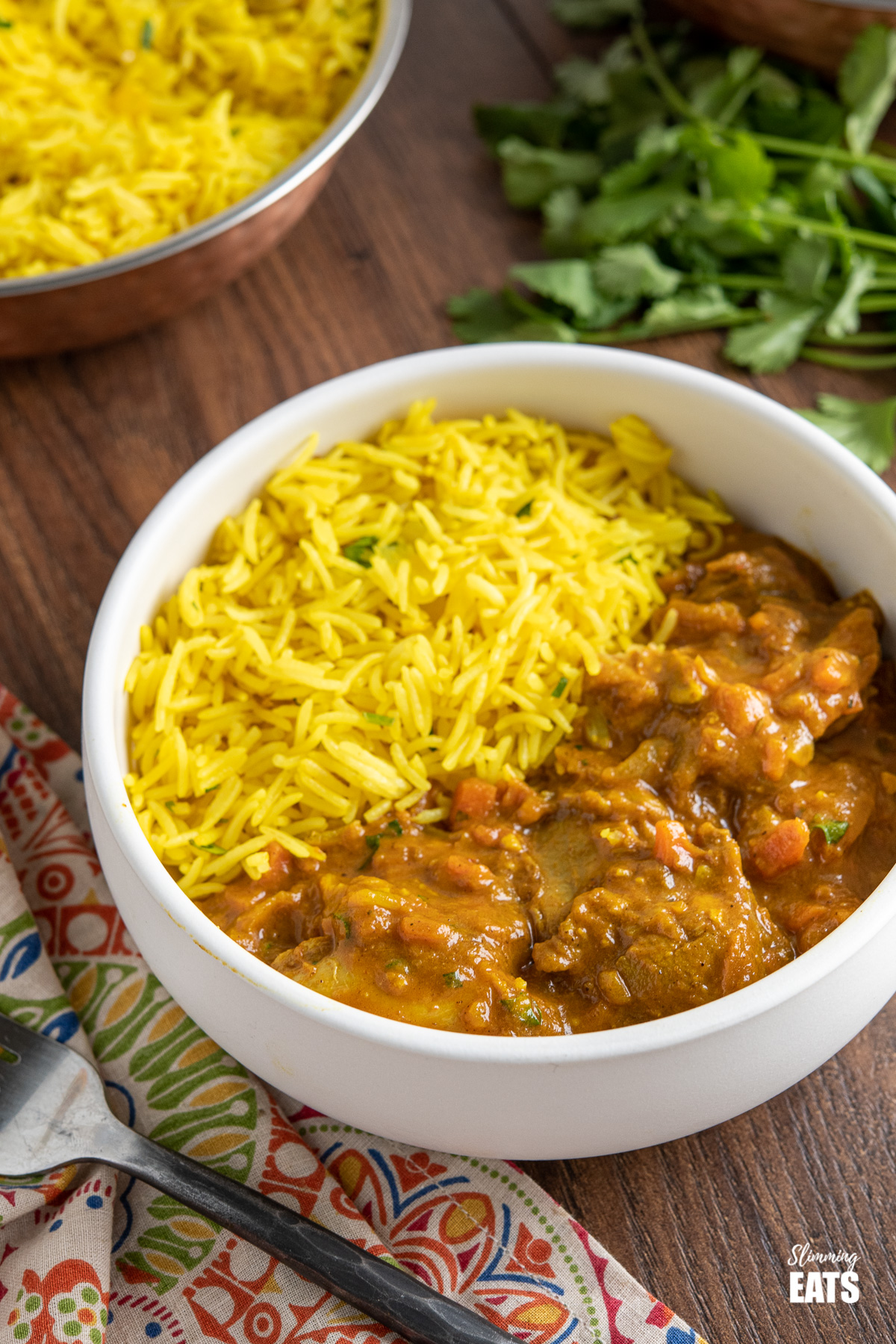 Chicken Dupiaza with pilau rice in a bowl with rice and coriander in the background