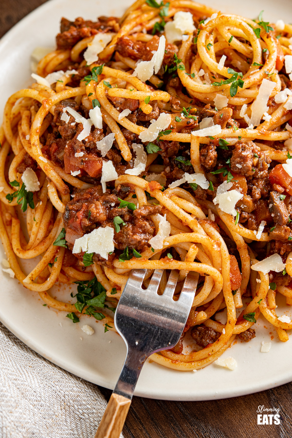 close up spaghetti bolognese on plate with fork and shavings of parmesan on top