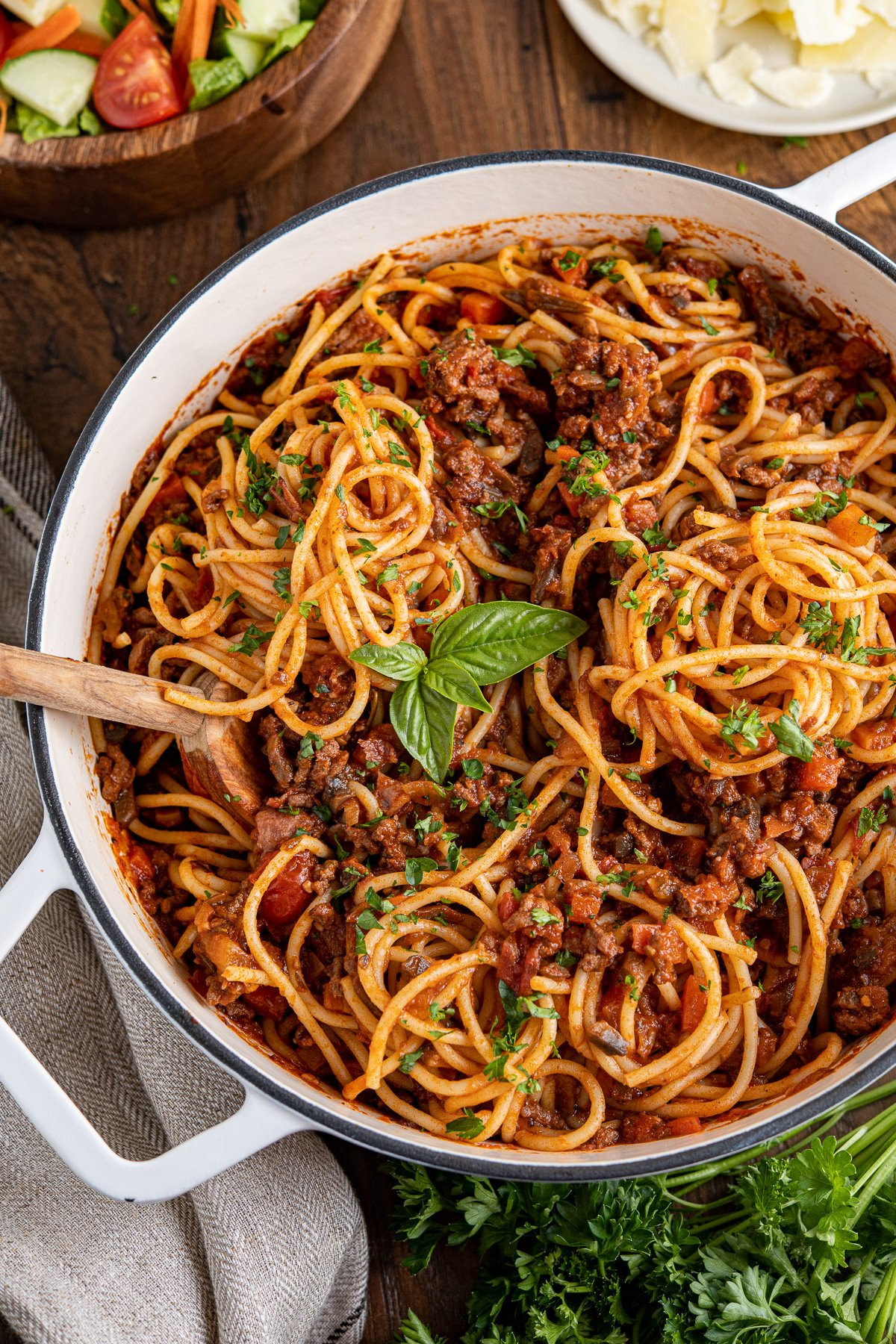 spaghetti bolognese mixed up in a white cast iron pan top with parsley and basil, bowl of salad and plate of parmesan in the background