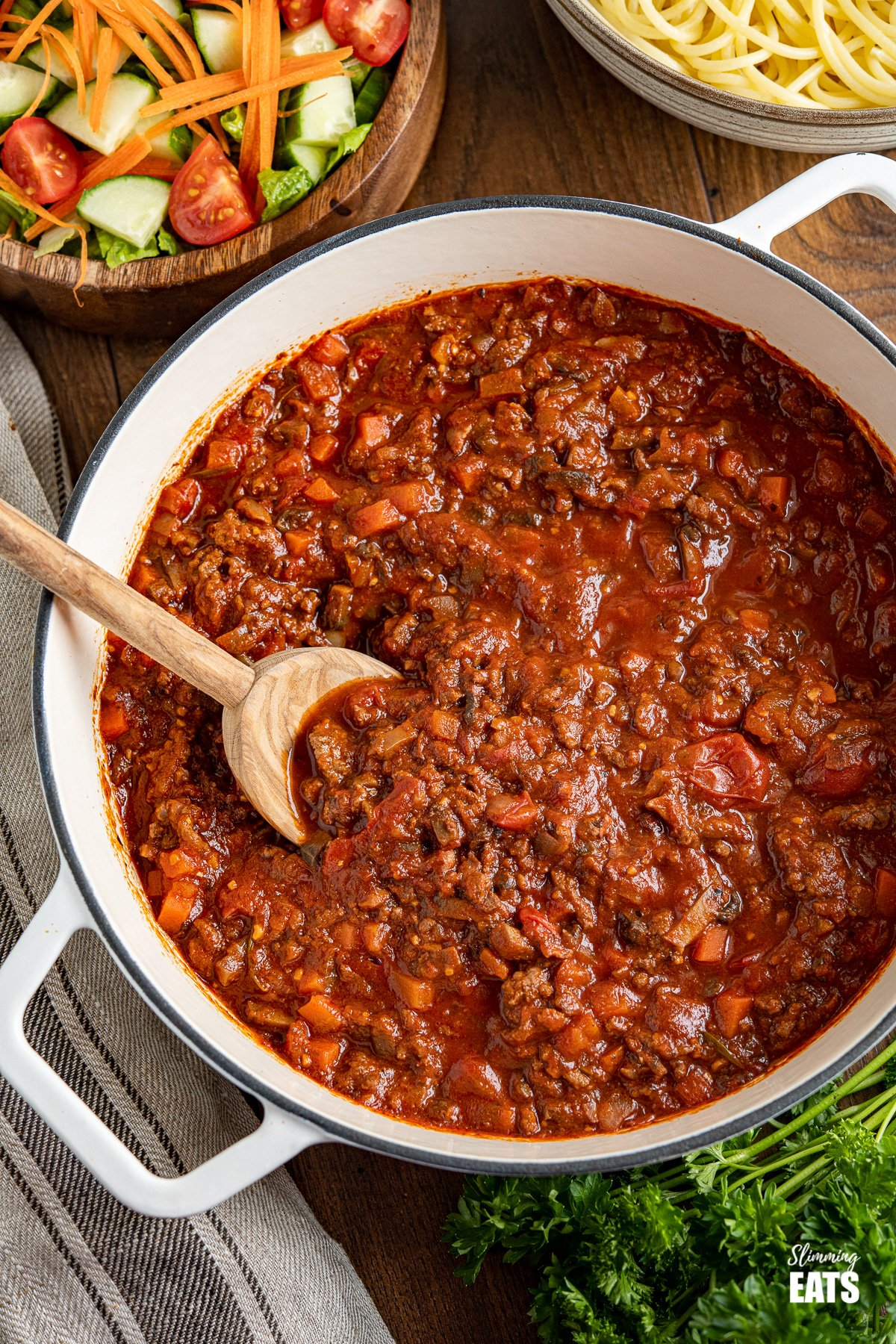 Bolognese meat sauce in white cast iron casserole pan with wooden bowl of salad and bowl of spaghetti in background
