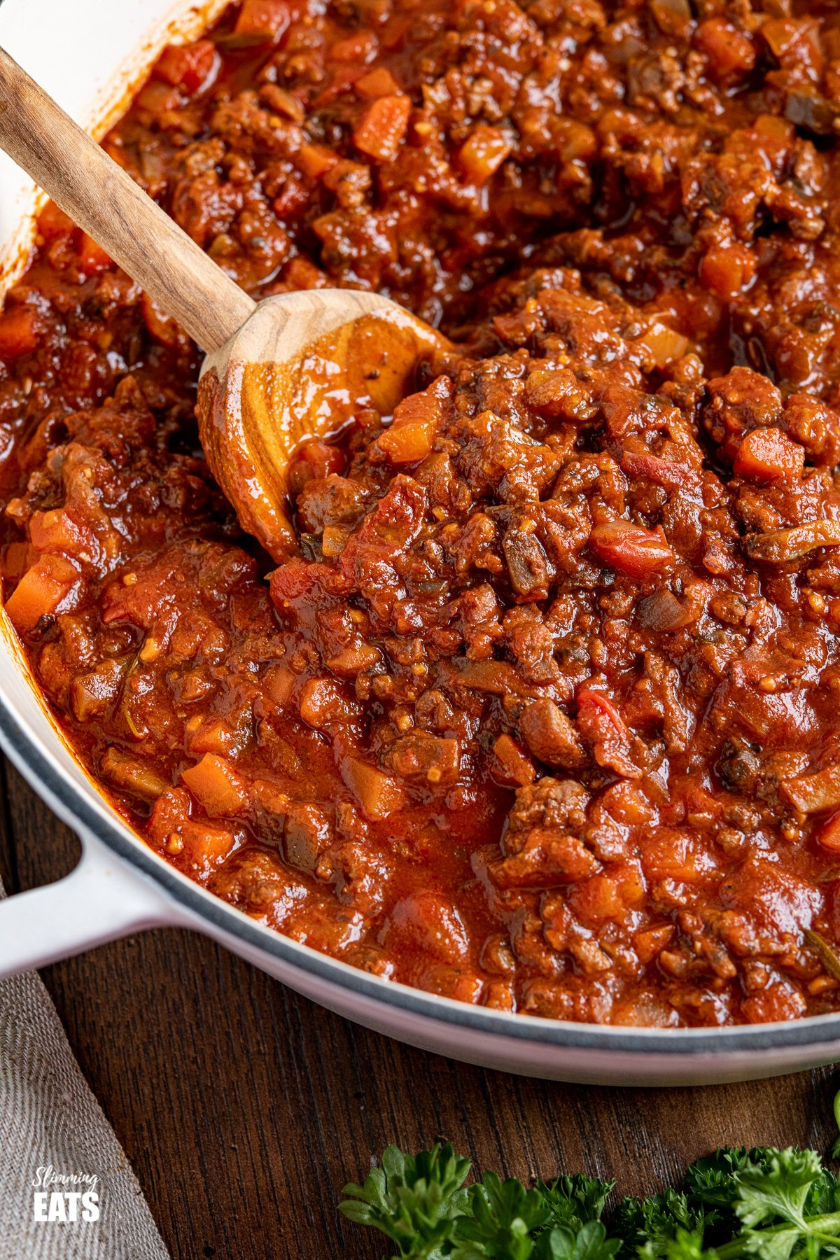 close up of bolognese meat sauce in white cast iron pan with olive wood spoon