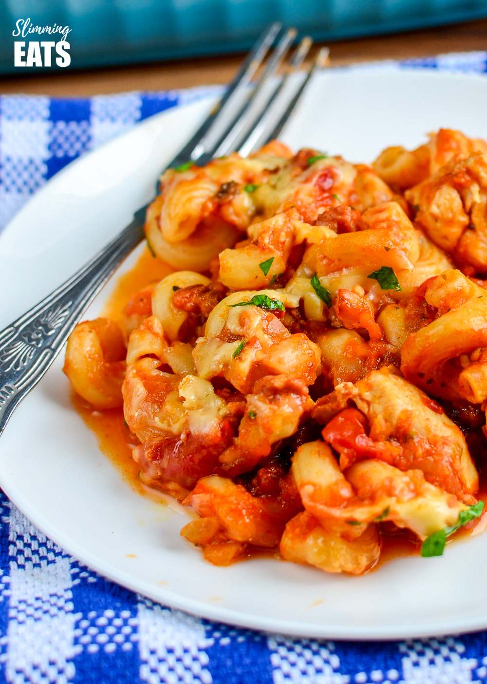 chicken bacon and tomato pasta bake on white plate with fork