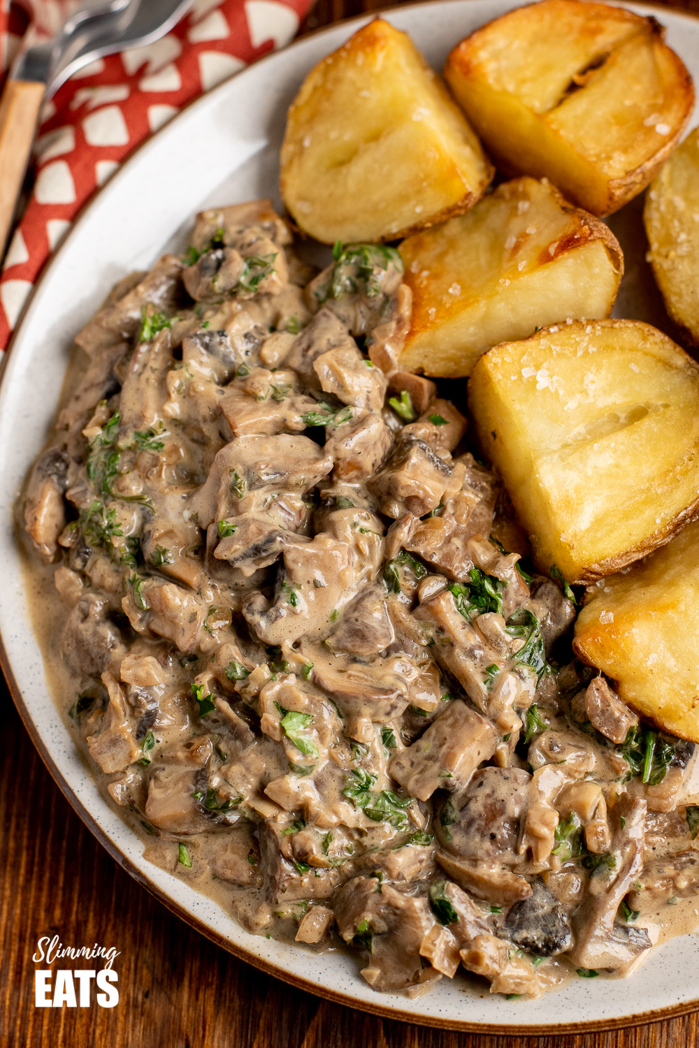 close up of creamy garlic mushrooms on plate with roasted jacket potatoes.