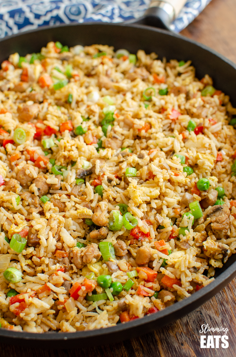 chicken fried rice in a frying pan on a blue pattern placemat and wooden board