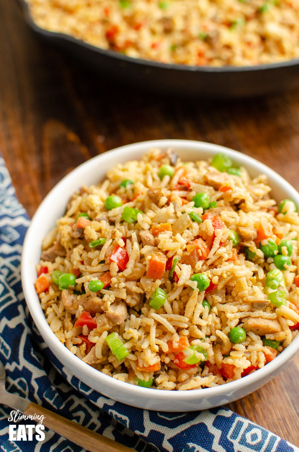 chicken fried rice in white bowl on wooden board with blue patterned placemat