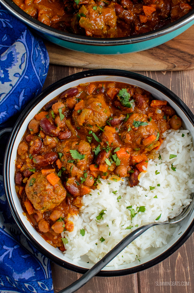 over the tip view bowl of lamb meatball and bean curry with rice with fork