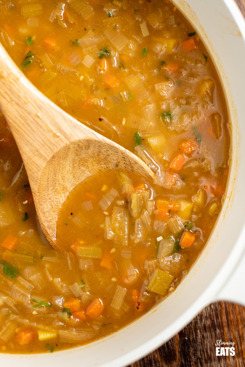 close up of hearty vegetable soup in pan with wooden spoon