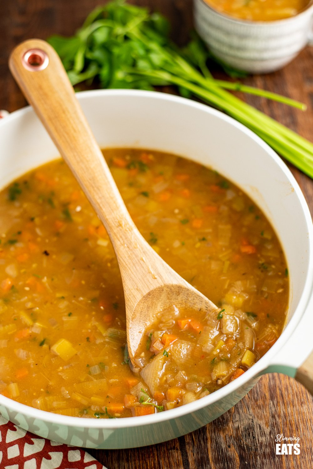 hearty vegetable soup in pan with wooden spoon