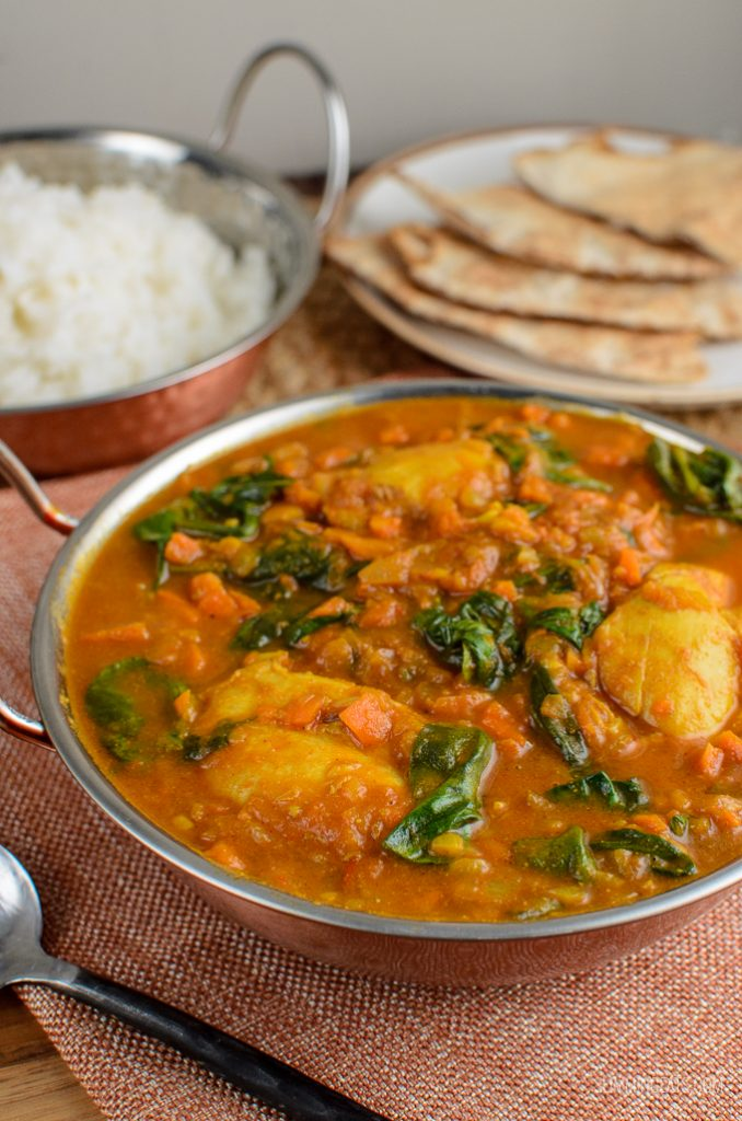 chicken and spinach curry in a dish with rice and bread in background