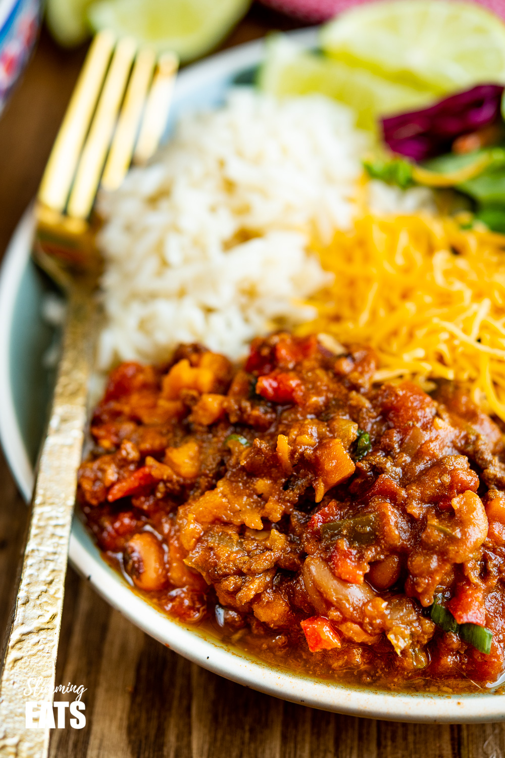 close up of beef and six bean chilli on green blue plate with gold fork