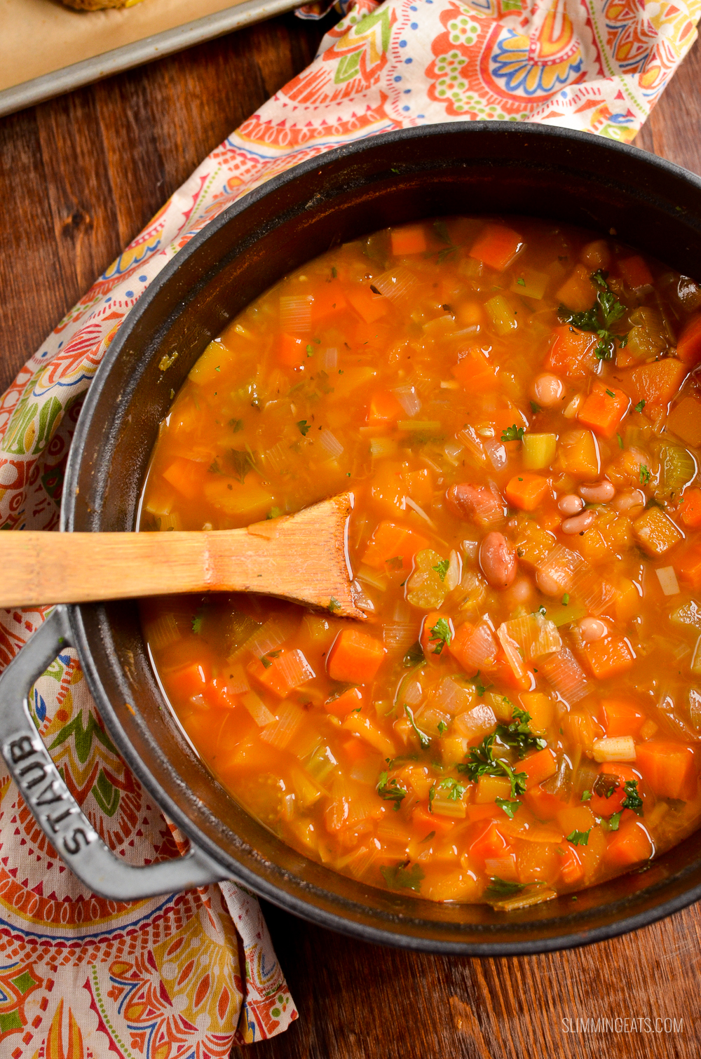 vegetable and bean stew in cast iron pot with wooden spoon