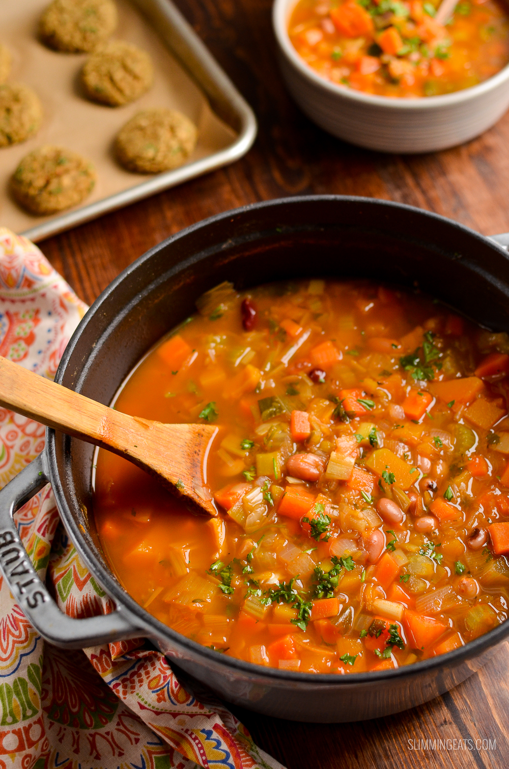 vegetable and bean stew in a cast iron pot with dumplings in background