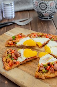 sliced breakfast hash brown pizza with coffee and knife and fork