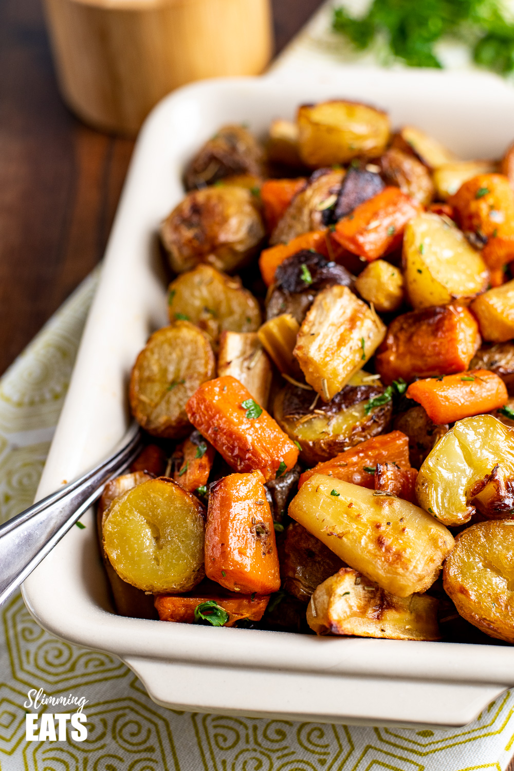 Rosemary Roasted Potatoes, Parsnips, Carrots and Onion in dish with metal spoon